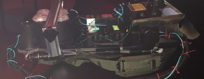 Ghostbuster Proton Pack laying flat on a table in a dark room
